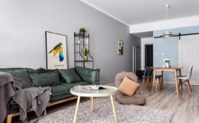 墙面由纯白、高级灰和天空蓝组成,干净明亮 的配色为全屋奠定了良好的视觉基础。以大件 家具的墨绿来沉淀空,辅以原木、暖棕增加空间温馨度